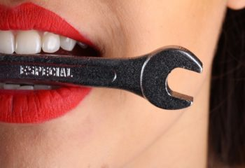 close-view-of-woman-with-red-lips-biting-gray-special-wrench-1161929